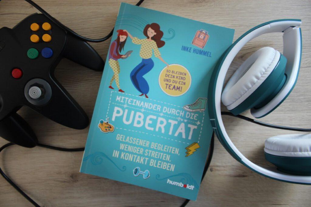 """Das Buch """"Miteinander durch die Pubertät"""" von Inke Hummel liegt zwischen einem Controller und einem Headset-Kopfhörer"""