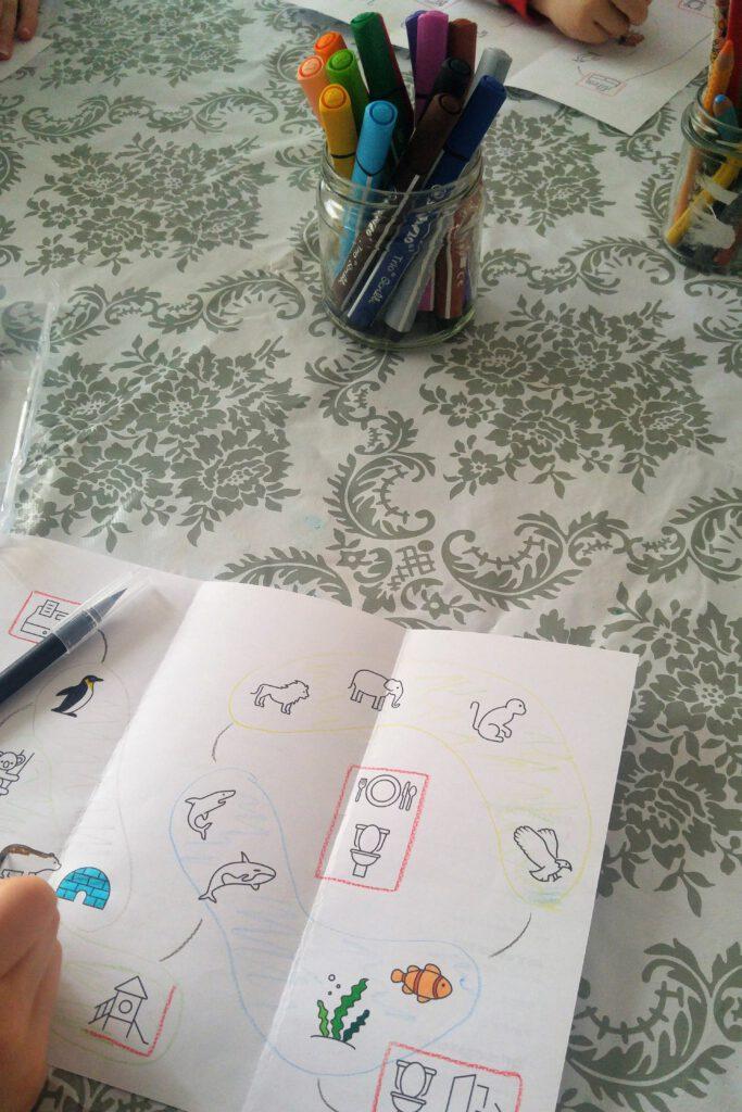 Auf einem TIsch ist eine gemusterte Unterlage ausgebreitet. Darauf stehen Gläser mit Stiften. Zwei Kinder malen selbstgemachte, ausgedruckte Zooflyer an, auf denen verschiedene Tiere als Strichzeichnungen abgebildet sind.