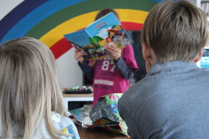 Zwei Kinder von hinten. Vor ihnen, im Bild mittig, steht ein weiteres Kind und liest aus einem Buch vor.