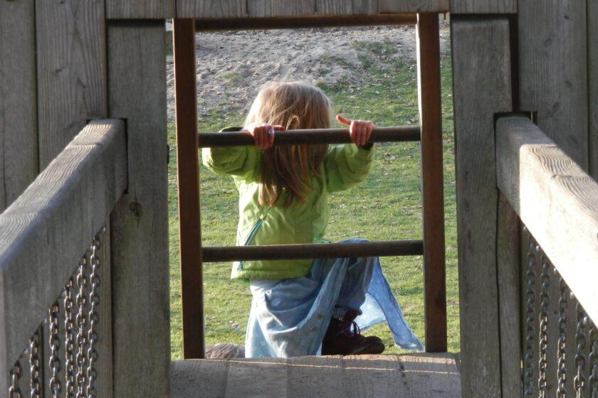 Ein Kind mit mittellangen blonden Haaren, grüner Jacke, blauem Rock und dunklen Stiefeln steigt eine Leiter an einem Spielgerüst hoch.