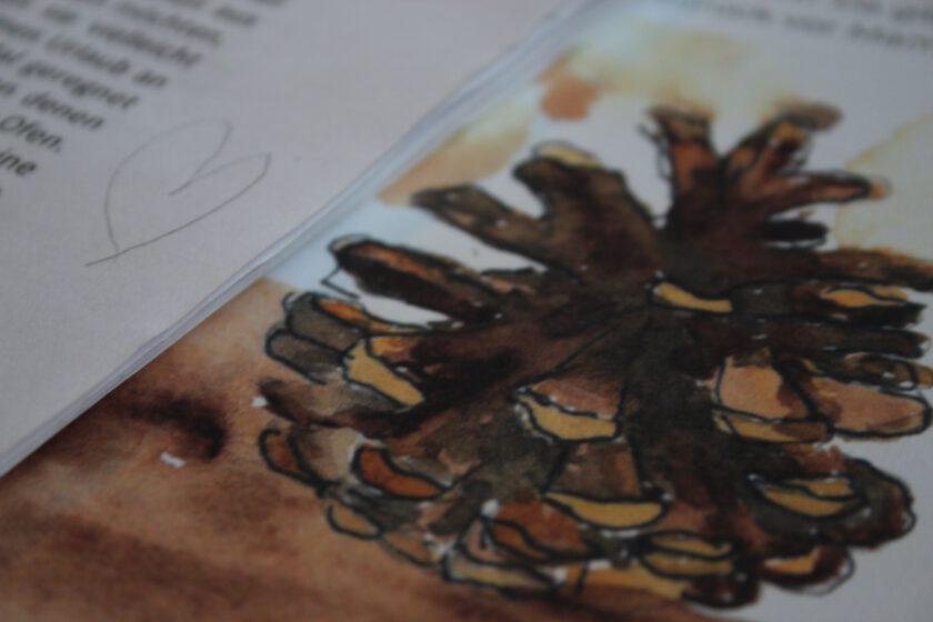 """Nahaufnahme einer Illustration aus """"Der Mönkel und der Trillfox im Moor"""". Darüber liegt das ausgedruckte Manuskript des Buches."""