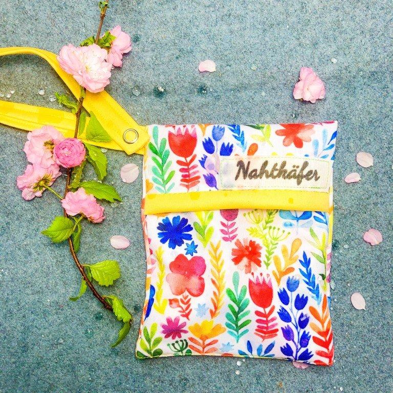 Nahtkäfer Mini Wetbag im Blumen Design auf grauem Wolluntergrund, dekoriert mit rosa Blüten